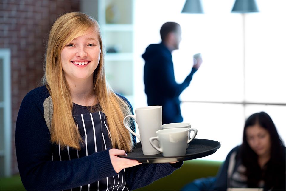 Girl holding tray with coffee mugs on it.