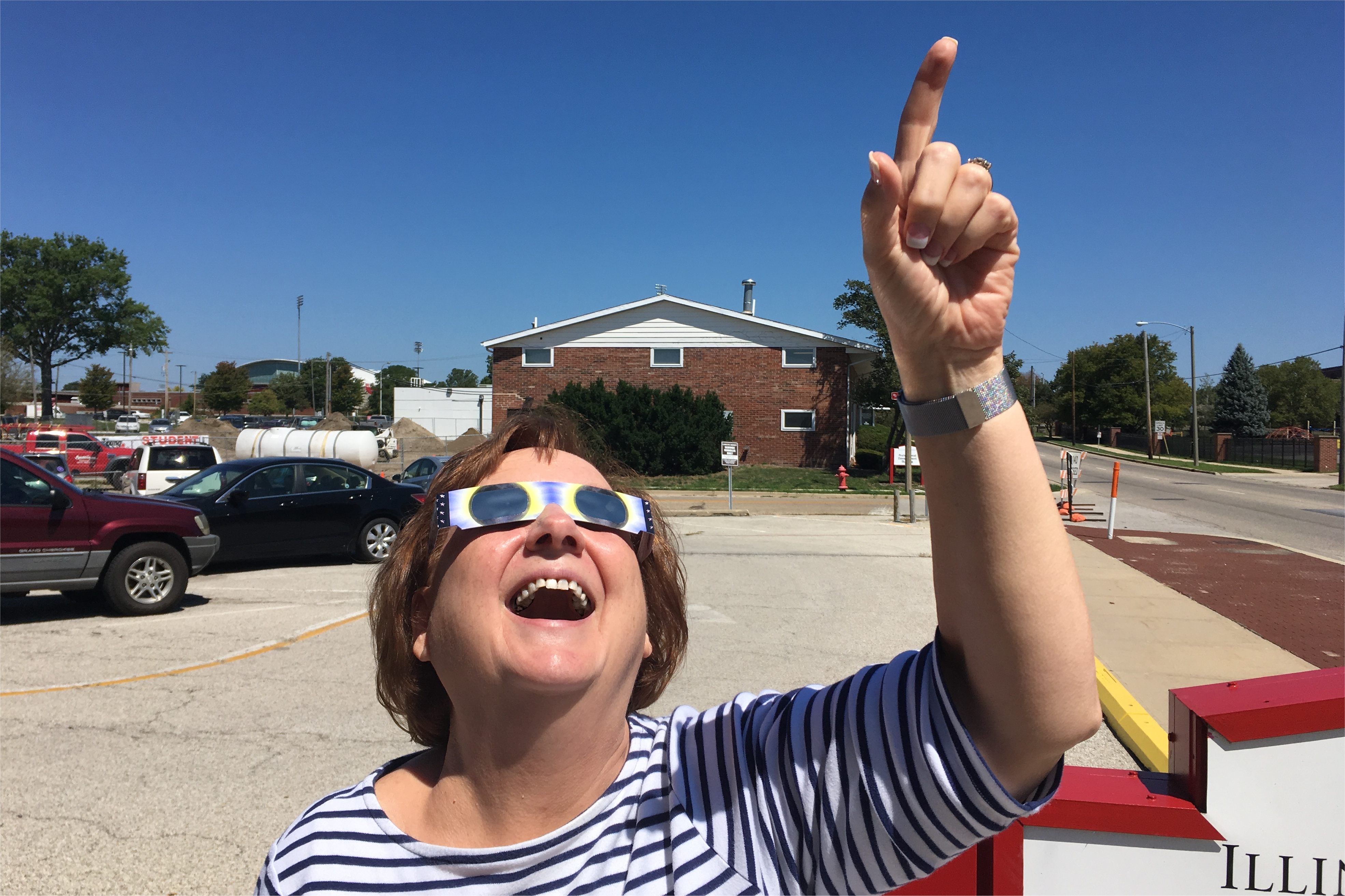 Dr. Claire Lamonica looks up at the sun, safely.