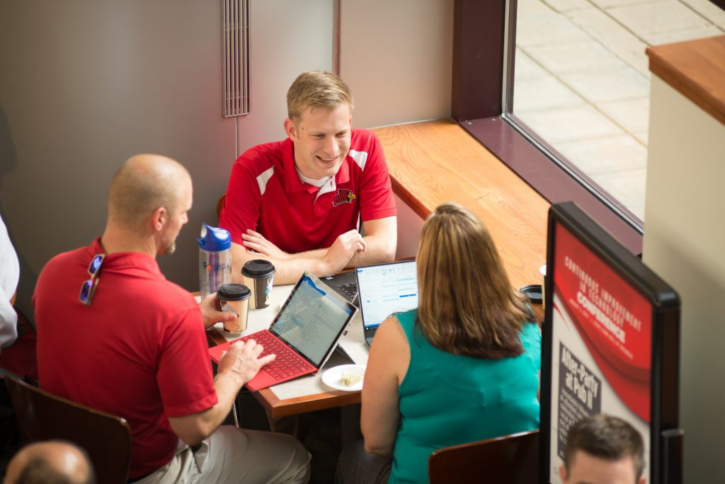 Three IT staff conversing at CIT 2017.