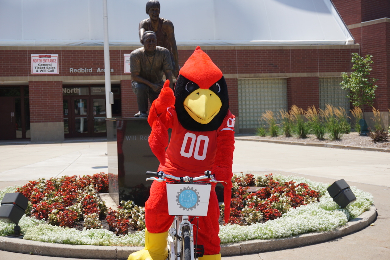 Reggie Redbird rides a bike from the Town of Normal's rental program, Bike Share 309.