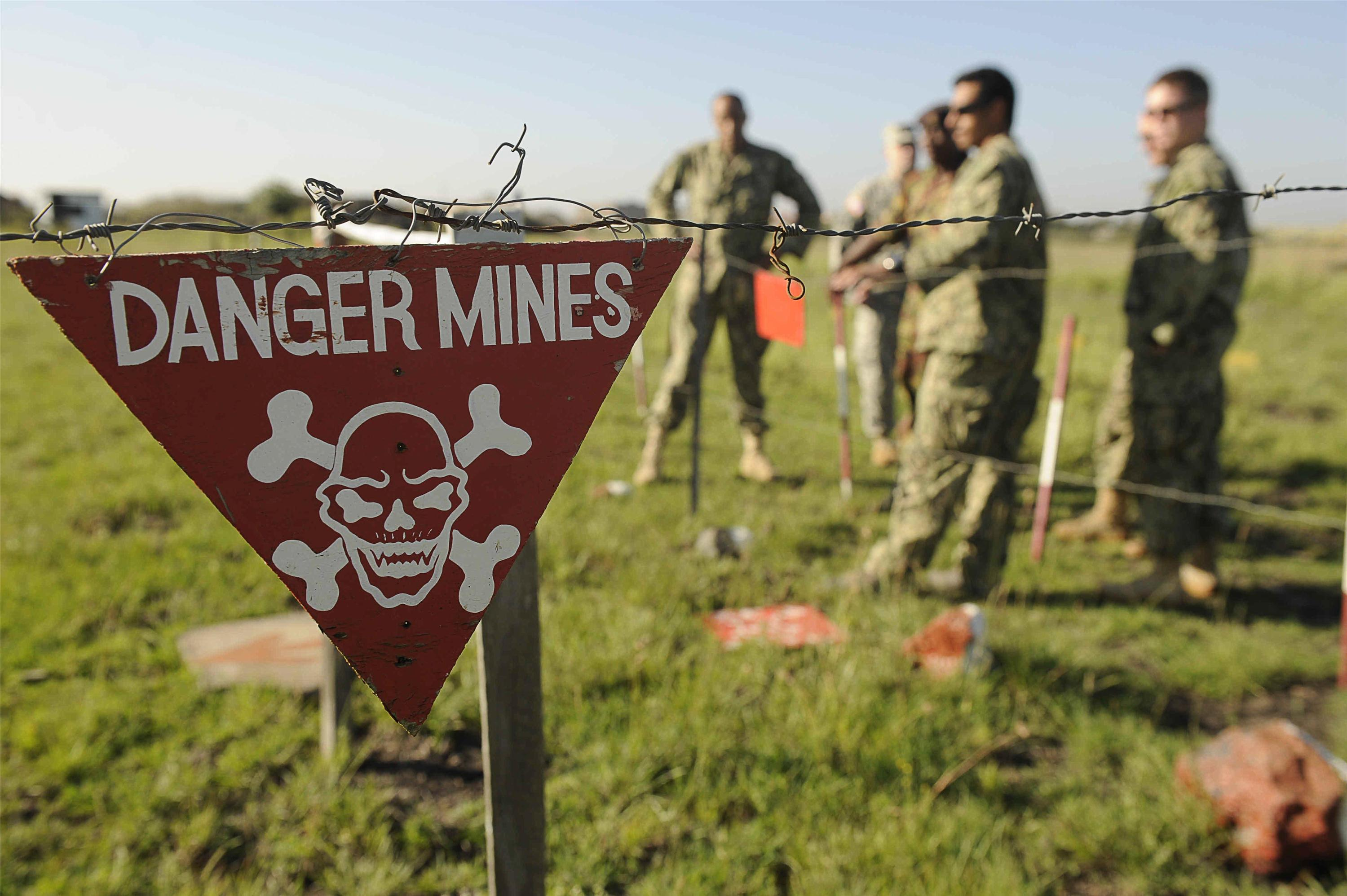 sign warning of landmines with soliders in the background.