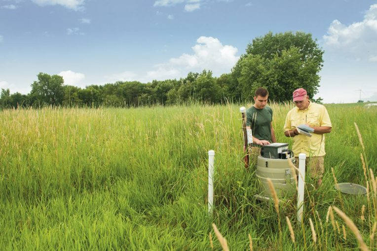 Professor Eric Peterson and graduate student Joe Miller set up a collection device near a tributary of Lake Evergreen to determine nitrate levels in the groundwater.