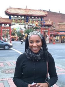 a woman standing in front of Chinatown, smiling