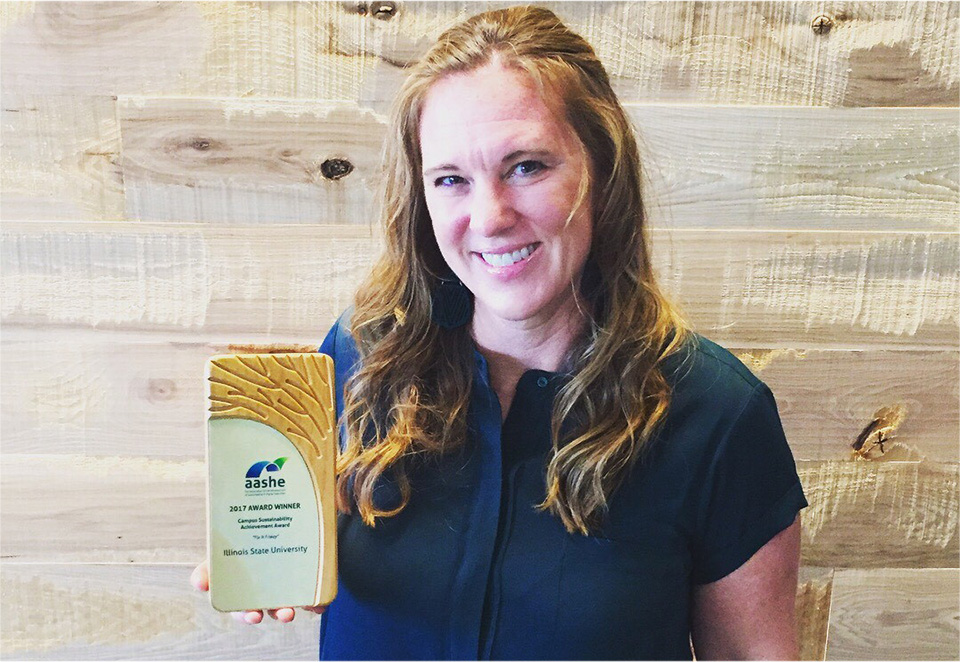 Elisabeth Reed holds an award from the Association for the Advancement of Sustainability in Higher Education.