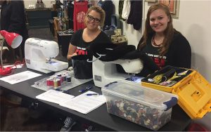two students at sewing machines, surrounded by buttons and items for fixing clothes.