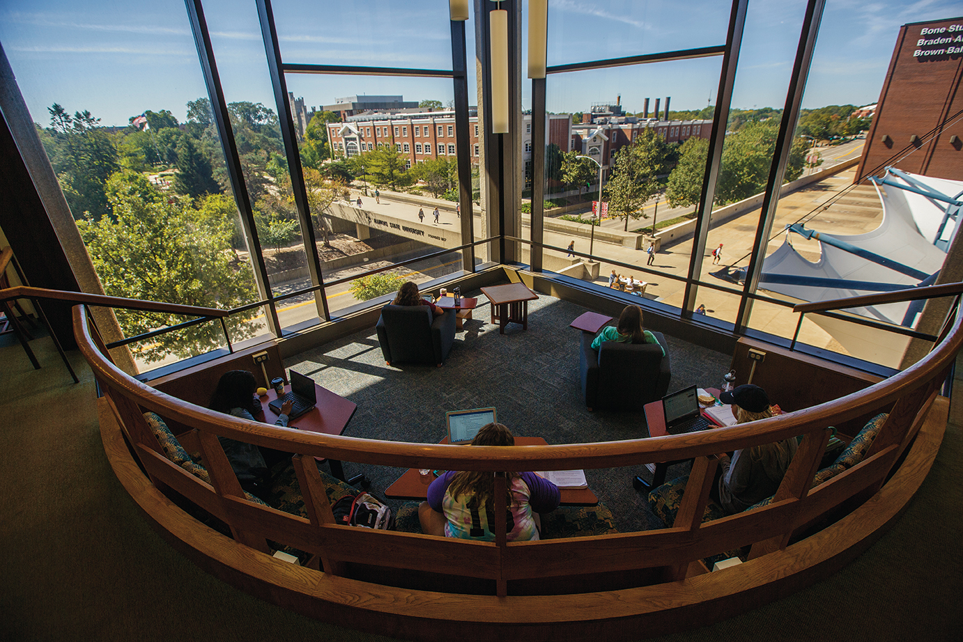 Looking out a corner window of Milner Library onto the Quad. Students seated in chairs working.