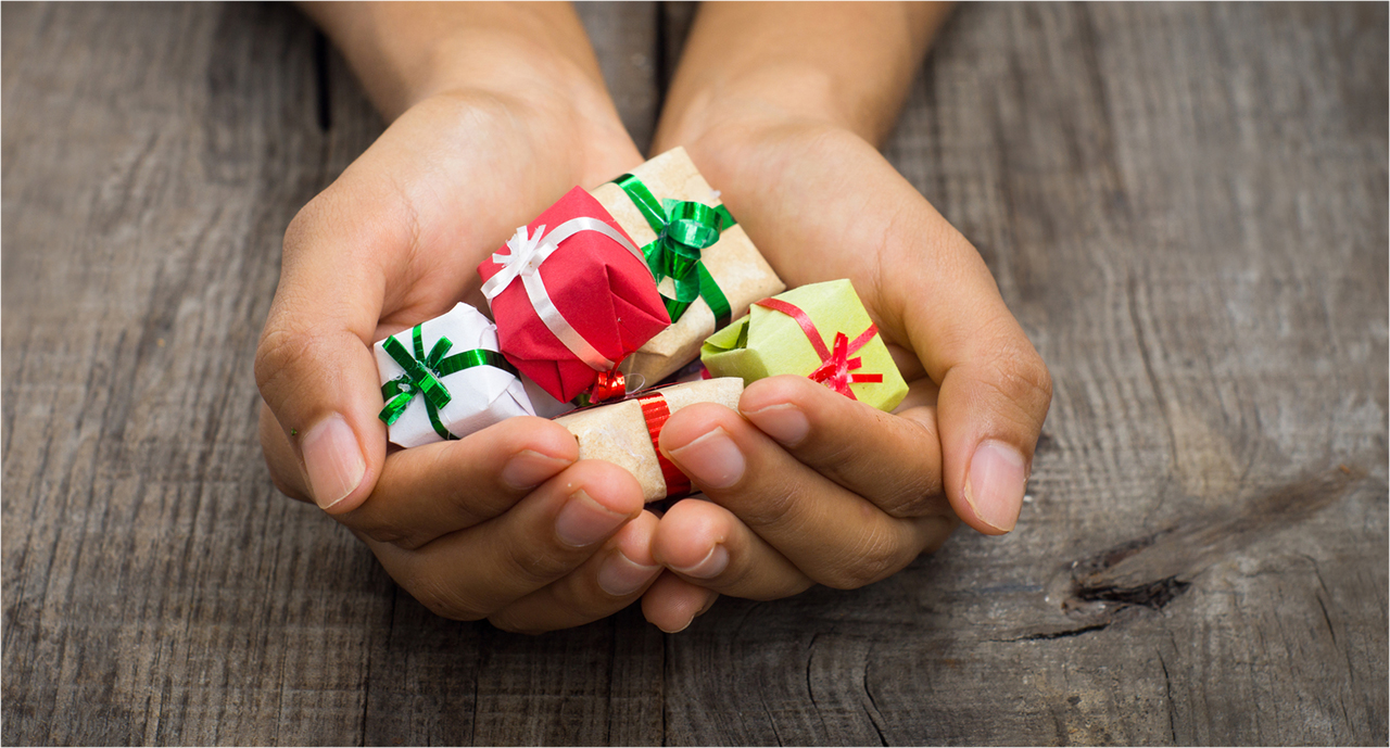 hands holding tiny gifts with smooth ribbons on them