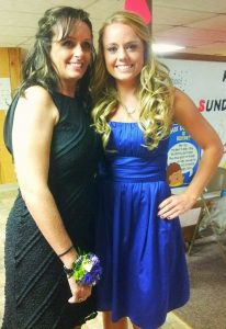mother and daughter, posing in dresses with the mother wearing a corsage