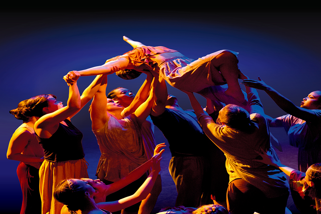 Image of group of dancers lifting one dancer