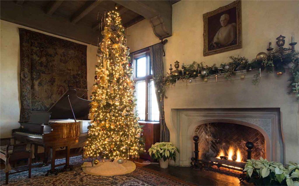 christmas tree near a grand piano and fireplace covered in garland and ornaments