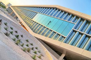 Domineering glass and concrete structure shaped in a diamond with sparse vegetation outside.