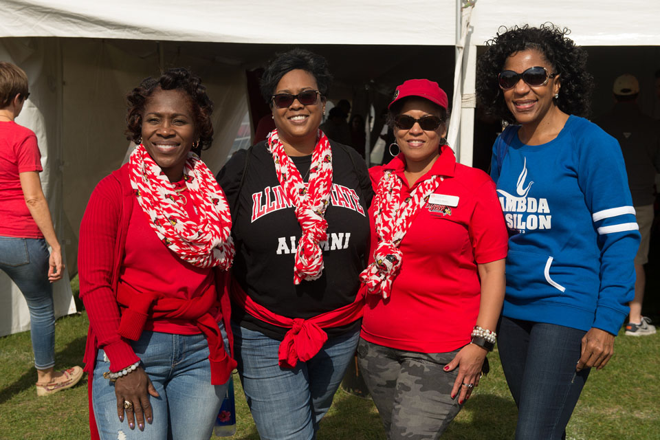 Four women smile at tailgate