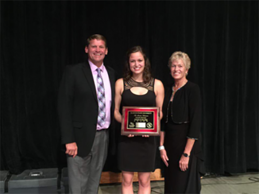 Rachel Root (center) receives award, flanked by a man and a woman.