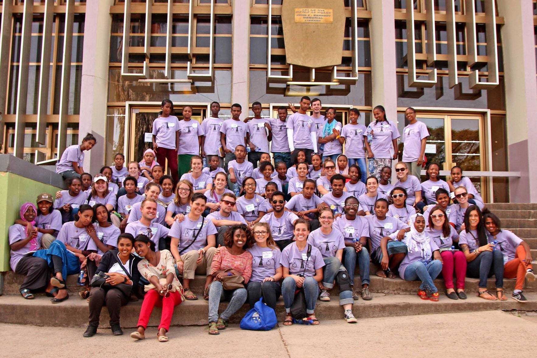 Alesha Klein and others wear purple shirts on the steps of a building in Ethiopia.
