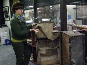 woman standing next to open steamer trunk