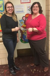 Student receives check from staff member
