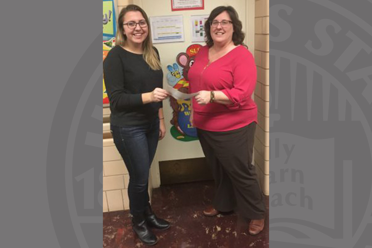 NSSLHA representative Melissa Jenkins receives a check from CSD staff member Tricia Larkin.