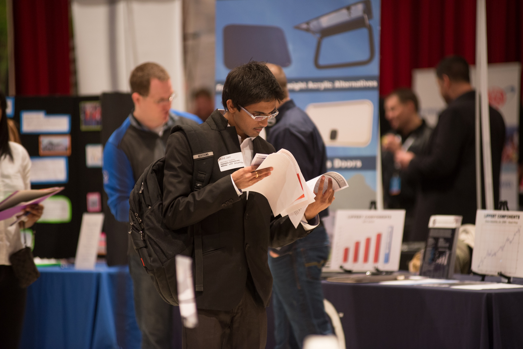 A male student looking through several flyers and pieces of paper at a Career Fair.
