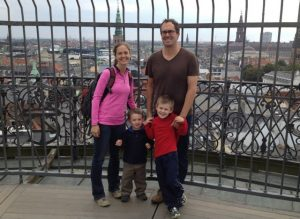tqo adulst and two children stand on a balcony with a wrought iron fence, a view of Denmark in the background