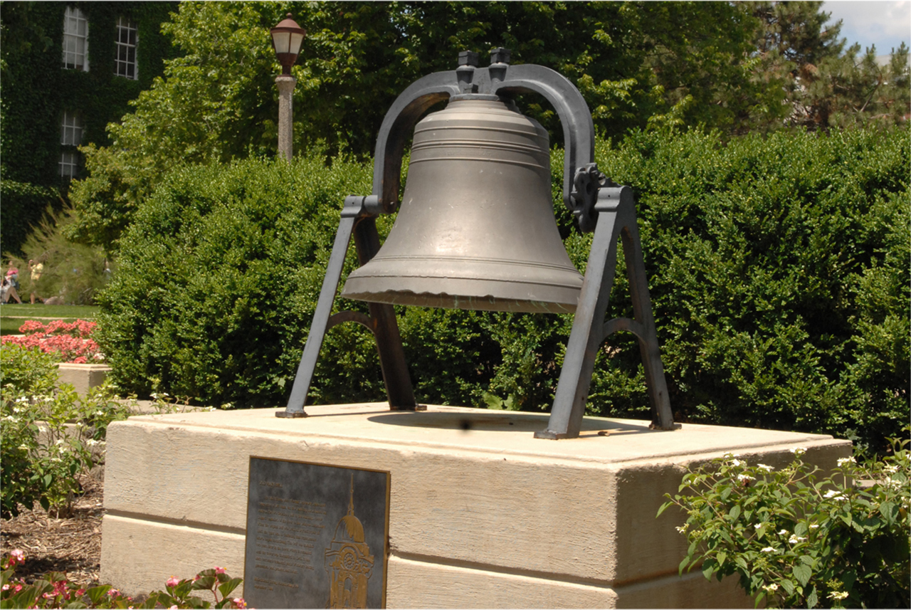 Large bell surrounded by flowers and set in stone landscaping, with trees and academic buildings in the background