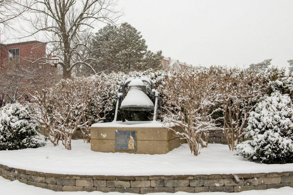 giant bell covered in show and surrounded by wintery landscape.