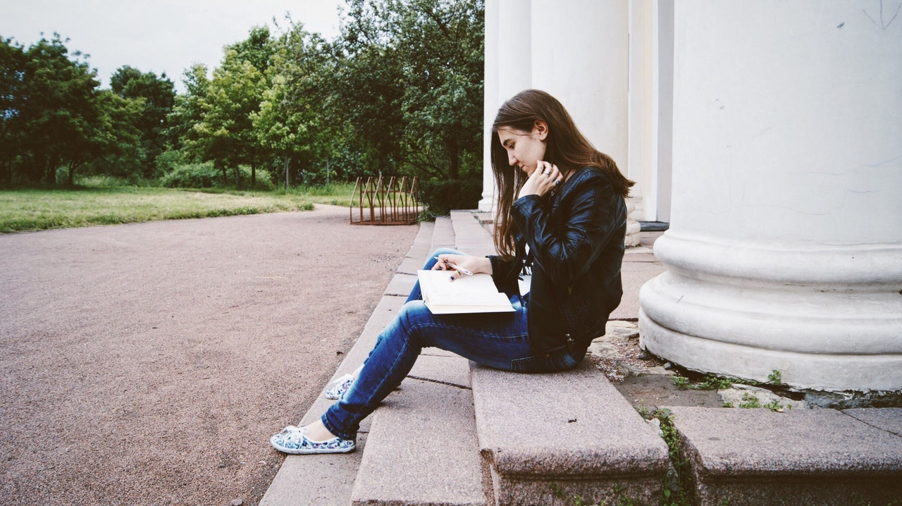 female college student reading on steps