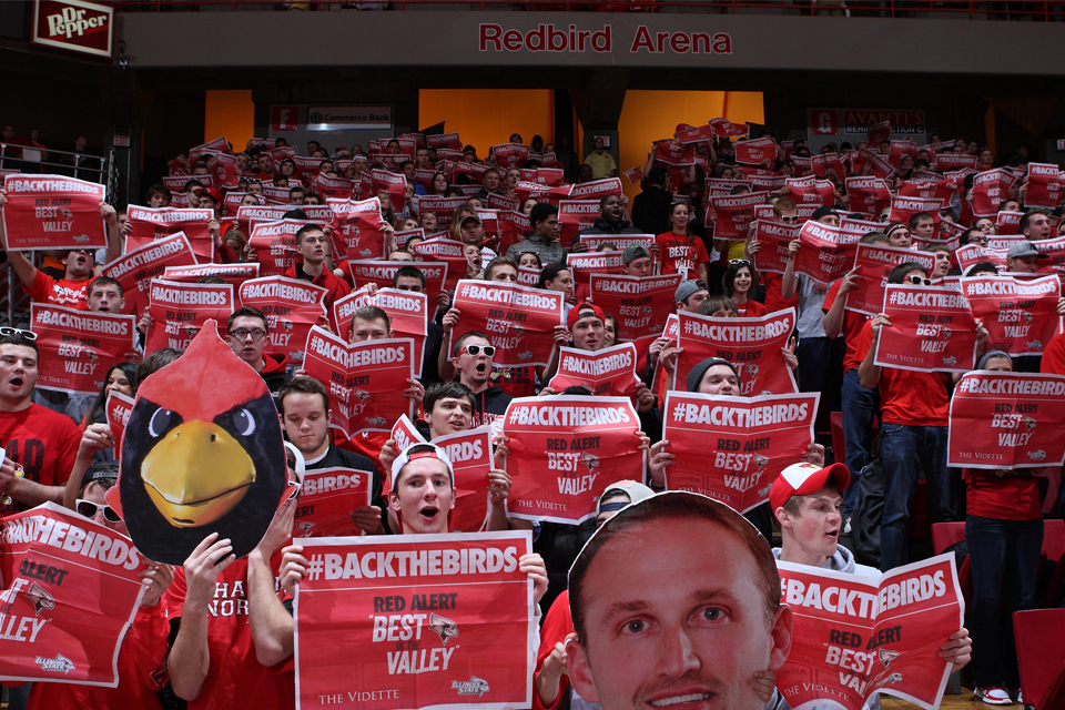 student section at basketball game holding newspapers