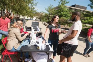 Jennifer Langner explains the free sewing repair service to a student on the Quad.