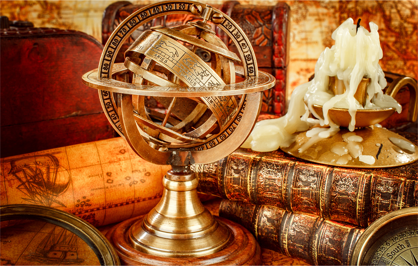 old sexton globe and books with a candle burned down to wax