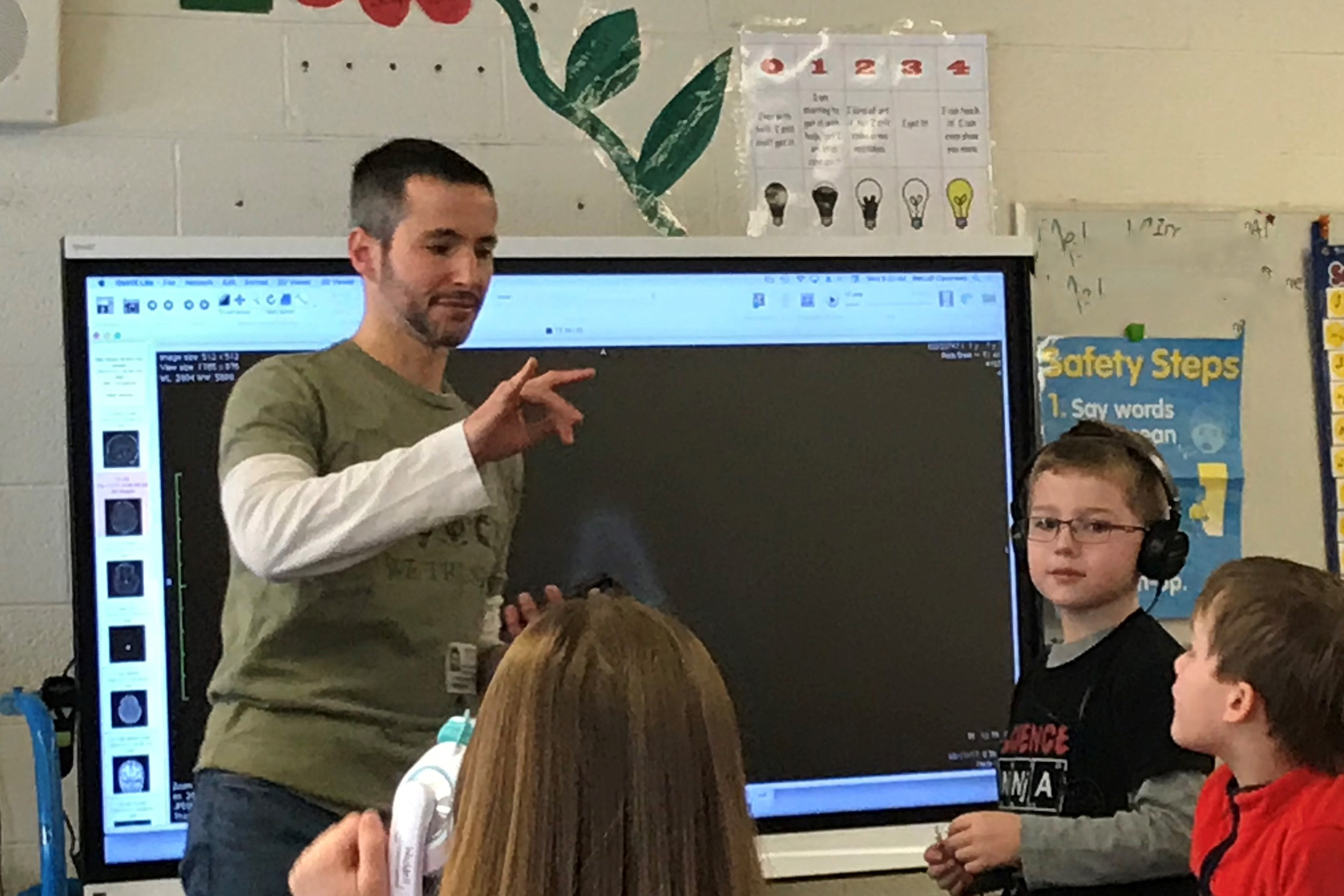 Jeff Wagman, Ph.D., PSY presents a short course on perception and the brain to second graders at Thomas Metcalf School. Connor Wagman, wearing headphones, helps with the demonstration.