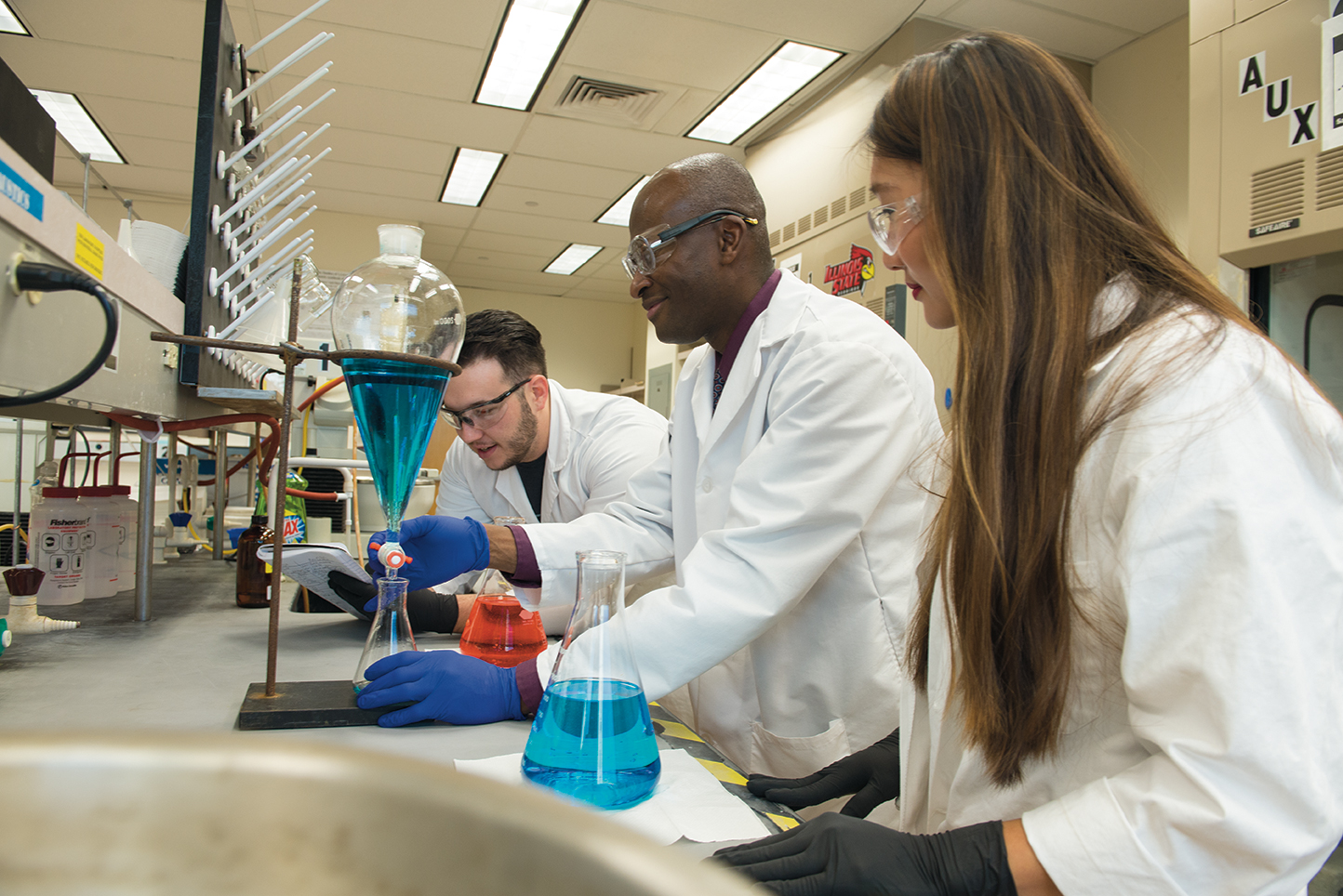 Professor Shawn Hitchcock (center) works in his research laboratory with students Stephanie Waggoner and Eric Jacobsen.