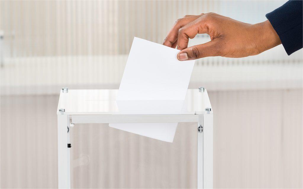 hand casting a ballot into a ballot box