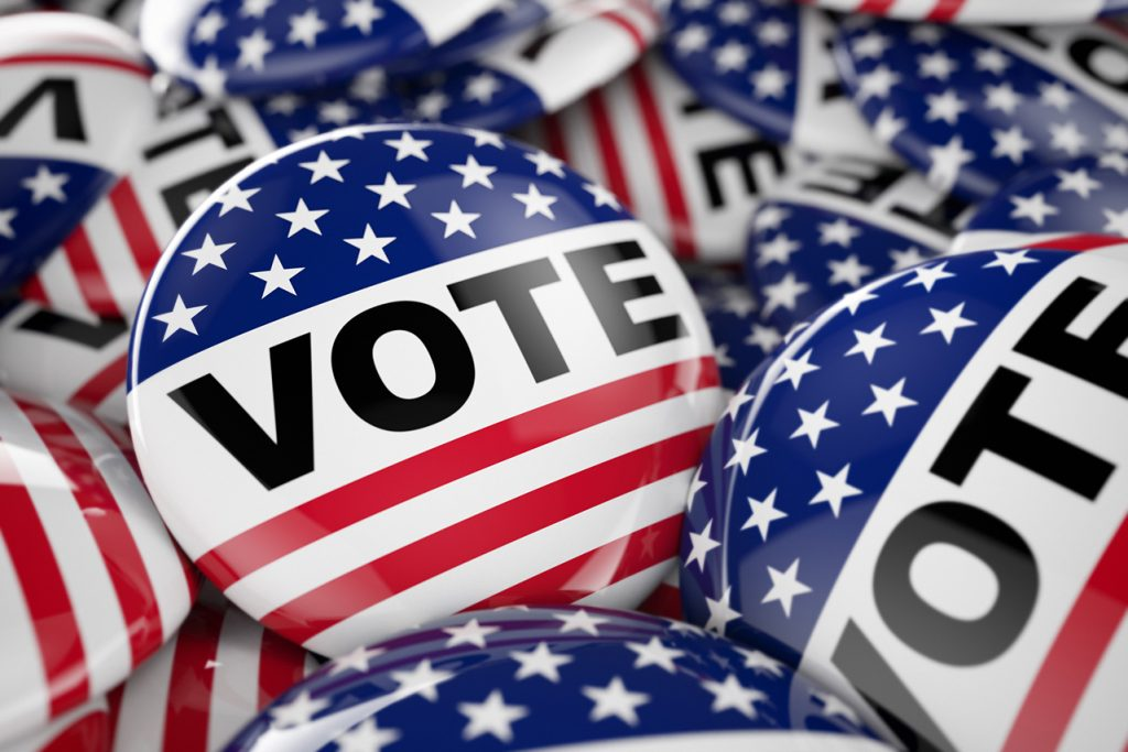 Image of buttons with the word VOTE on each, surrounded by the stars and stripes of the American flag.