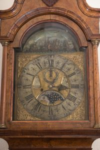 face of a clock with intricate metalwork in the shapes of masted ships.
