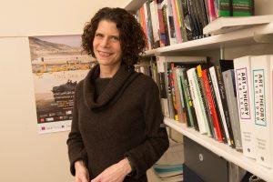 Associate Professor Elisabeth Friedman standing in front of shelves of books