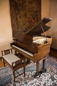 grand piano sitting in the foyer of the Ewing Manor on a rug with a tapestry hanging behind