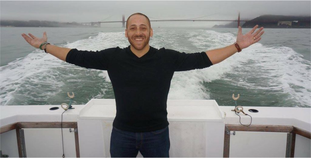 Man with arms outstretched, standing on a boat in the San Francisco Bay.