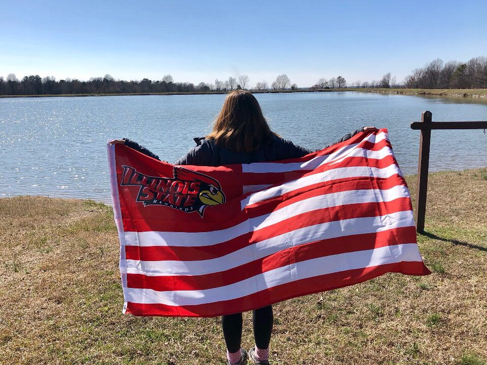 Student with ISU flag overlooking a lake