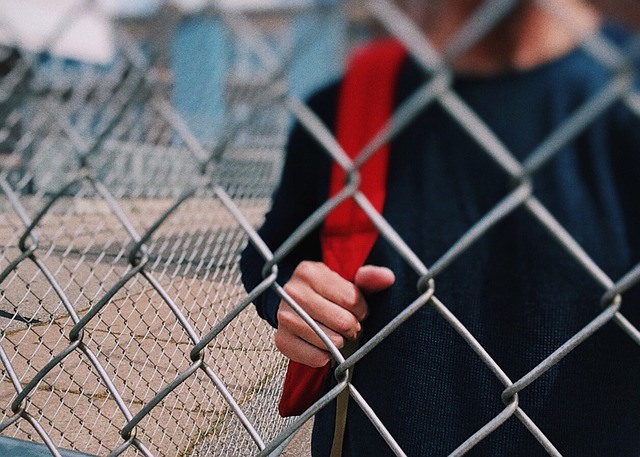 k-12 student behind fence with backpack