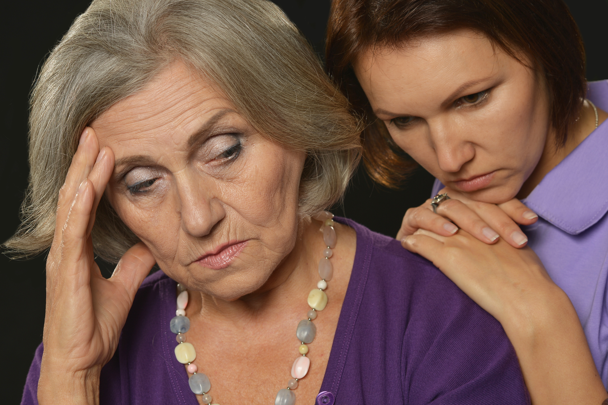 older mother upset and young woman leaning on her shoulder