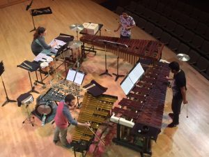 Four people playing avariety of percussion instruments on a stage. Shot taken from above them.
