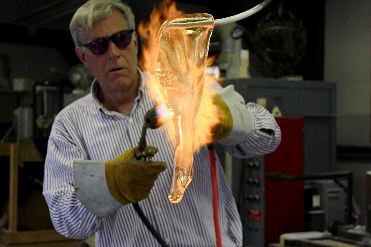 Image of alumnus Robert DuGrenier working with hot glass