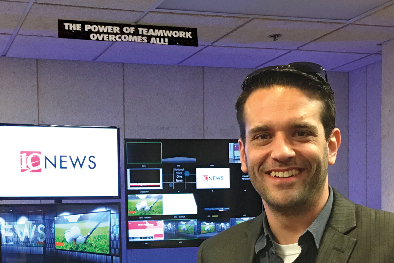 """Carlin Trammel '98 standing in front of the sign he hung at TV-10 back in 1996: """"The power of teamwork overcomes all."""""""