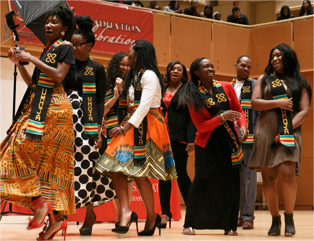 graduates dancing on stage as part of the Umoja celebration