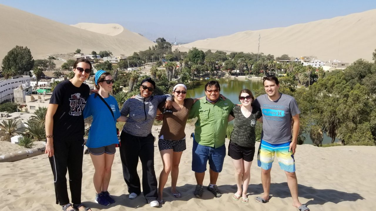 Group picture of students standing in front of an oasis in the desert, all are smiling.