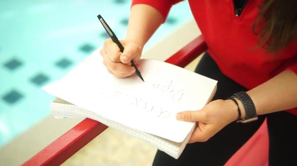 woman writing on a pad of paper with only the pad, her hands and her arms in focus.