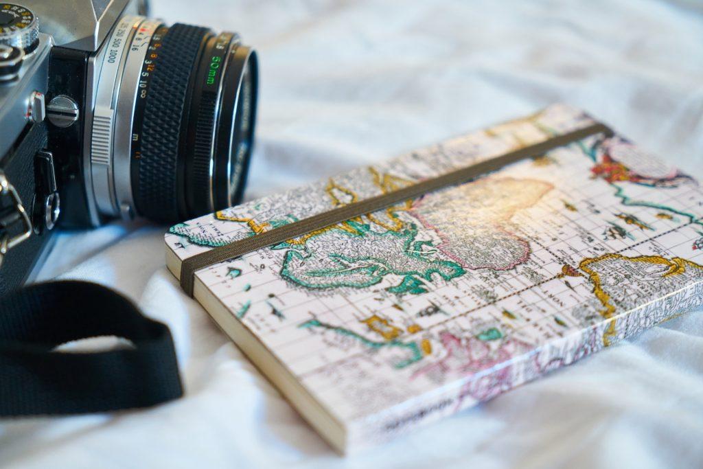 photography camera laying next to international notebook