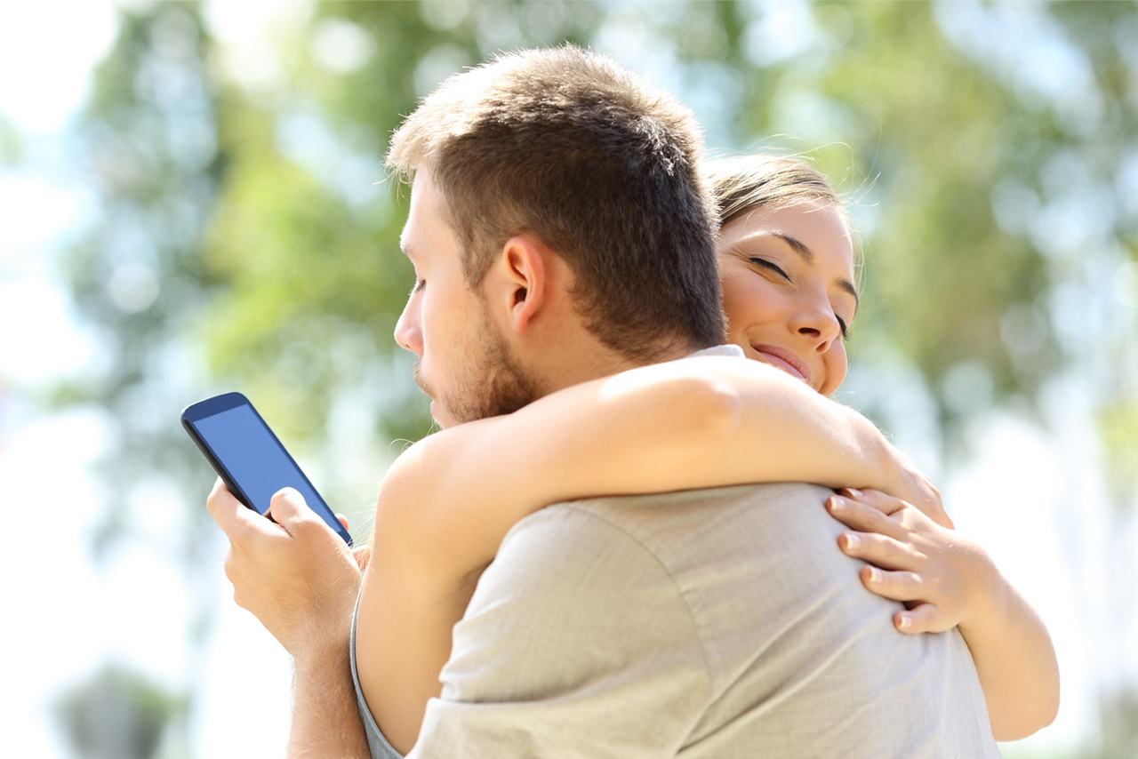 Man and woman embracing, but man looking at his cell phone