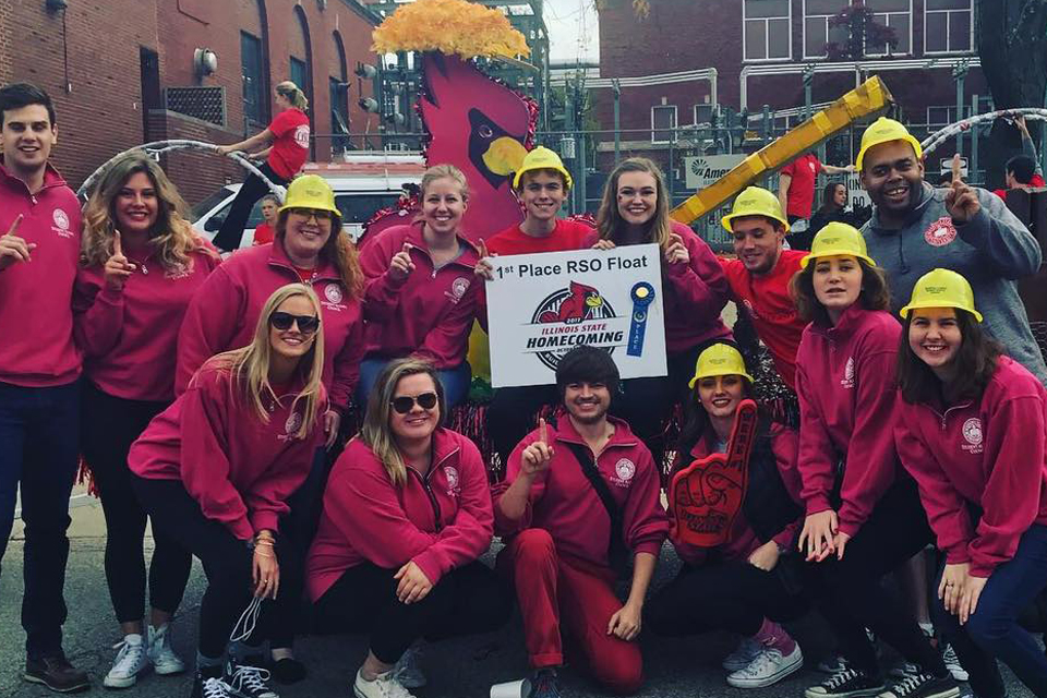 group of students with parade float and Redbird cutout