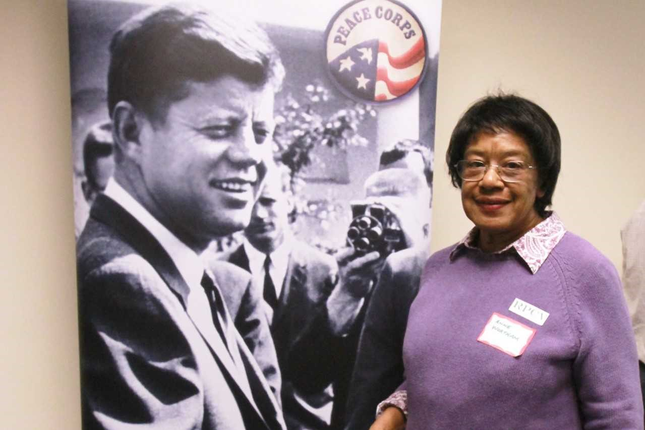 Anne Wortham next to Peace Corps poster of Kennedy
